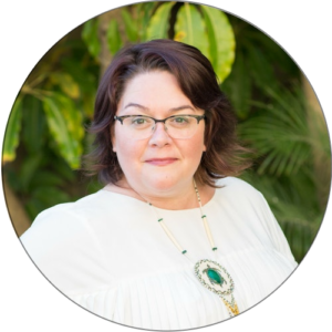Carmen Schreffler, marketing coach, wearing a white blouse and standing in front of some greenery. She is looking directly at the camera.
