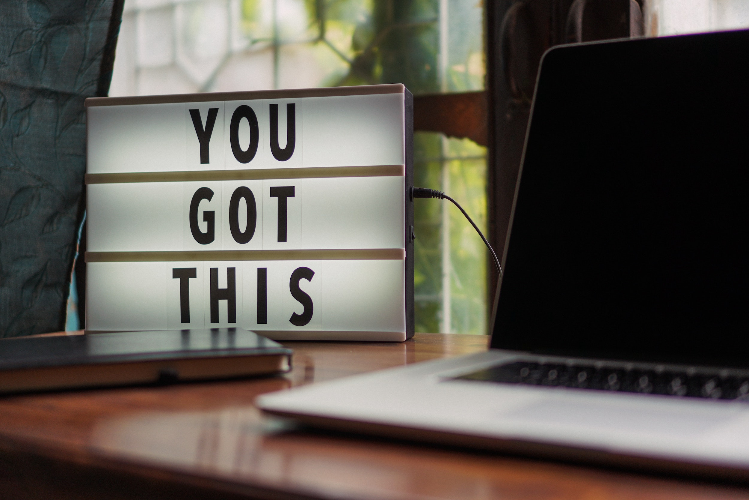 """A lightboard and laptop on a desk. The lightboard has the words """"You Got This"""". Photo by Prateek Katyal from Pexels"""