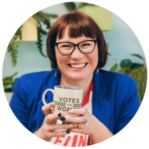 Jo Casey, smiling at the camera and holding a mug that says Votes for Women